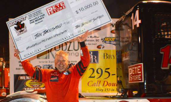 "Ricky ""Rude"" Proffitt holding Bandit big rig race winnings"
