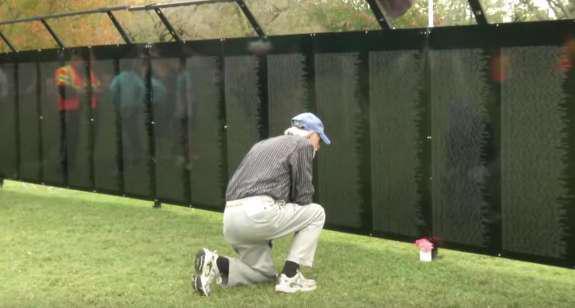 Man looking at the Vietnam Memorial Wall