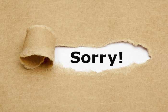 The,Word,Sorry,Appearing,Behind,Torn,Brown,Paper.